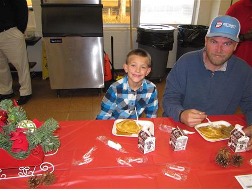 Student eats pancake and sausage breakfast with family at Santa Breakfast