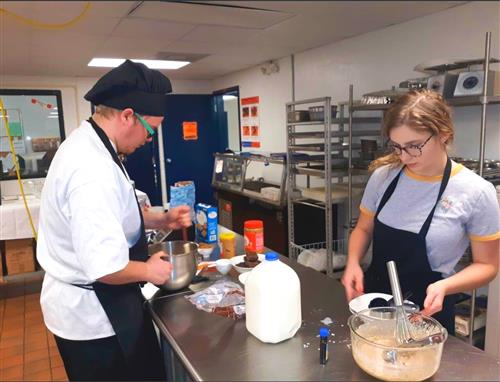 Two NFTC chefs prepare food.