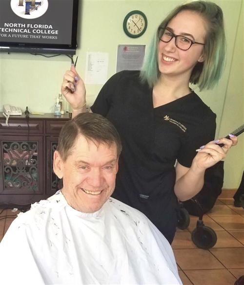 Cosmetology student poses with happy customer.