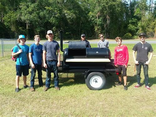 Welding class poses with the smoker they created.